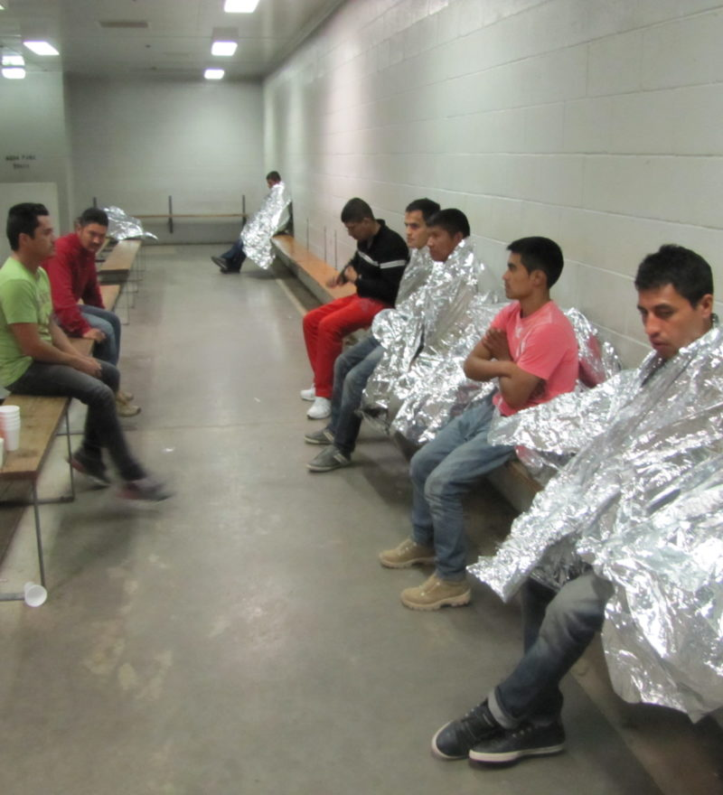 Detained migrants wearing space blankets